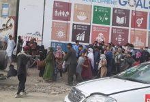 صورة شاهد ما فعله مقاتل من طالبان بمجموعة من النساء والأطفال أمام لوحة أممية في أفغانستان